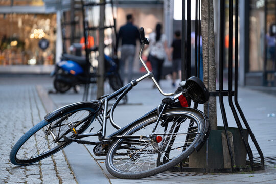 Black bicycle is half on the ground and half against a tree in a shopping street, parked carelessly or overturned. Fallen bicycle partly on the street and on the sidewalk