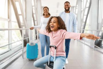 Fototapeta Happy black family traveling with daughter, having fun in airport obraz