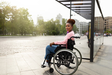 Obraz Young black handicapped woman in wheelchair cannot board vehicle suitable for impaired persons, waiting on bus stop - fototapety do salonu