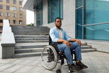 Obraz Portrait of unhappy black impaired man in wheelchair next to siatrs without ramp, feeling stressed, free space - fototapety do salonu