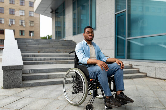 Portrait of unhappy black impaired man in wheelchair next to siatrs without ramp, feeling stressed, free space