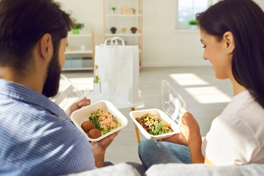 Happy people enjoying takeout lunch at home. Young couple sitting on sofa and eating fresh healthy takeaway food from plastic containers. Man and woman comparing two meals ordered in delivery service
