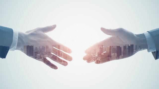 都市と握手するビジネスマン ダブルエクスポージャー