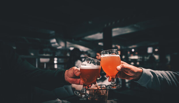 Closeup view of a two glass of beer in hand. Beer glasses clinking in bar or pub