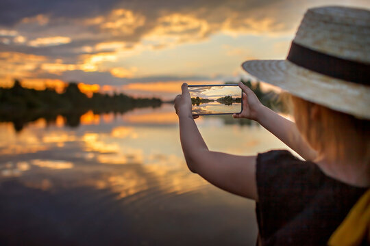 Pretty preteen girl in summer straw hat taking selfie for cellphone at beautiful sunset on lake, lifestyle, local travel concept, young blogger