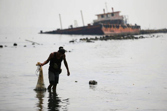 Fisherman carrying his net walks through the water while fishing, during World Oceans Day, at the shore of Jakarta