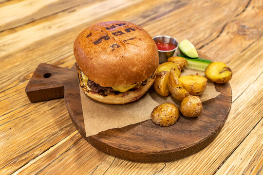 Burger with meat served with cucumbers, cetchup and fried baby potato on round cutting board. Unhealty dinner