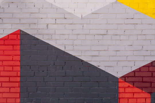Colorful grey, red, yellow brick wall as background, texture