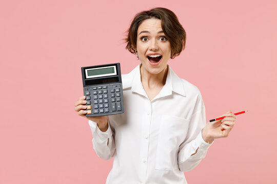 Young smiling successful employee business secretary woman corporate lawyer in classic formal white shirt work in office hold in hands calculator isolated on pastel pink background studio portrait