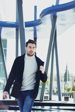 Stylish man with modern haircut walking in town