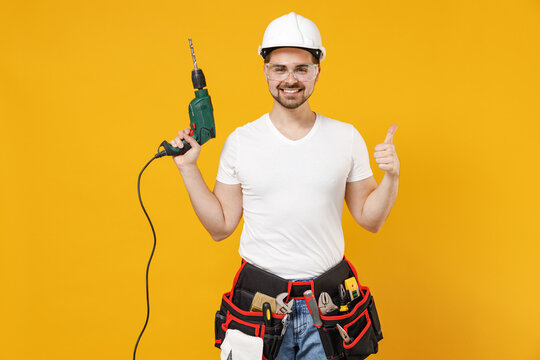 Young employee handyman man in protective helmet glasses hold electric drill thumb up like gesture isolated on yellow background. Instruments accessories renovation apartment room Repair home concept.
