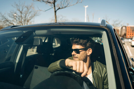 Masculine man driving car in town on sunny day