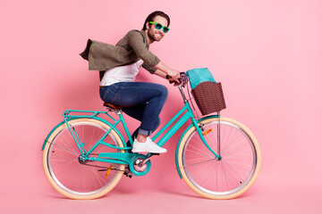 Photo of funky pretty young man wear brown shirt eyewear smiling driving cycle rucksack isolated...