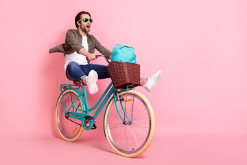 Obraz Photo of sweet cute guy dressed brown shirt dark eyeglasses riding bike backpack looking empty space isolated pink color background - fototapety do salonu