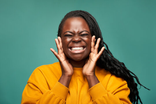 Content black woman holding face in hands in studio