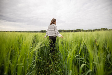 Obraz Happy woman walking in green rye field and enjoys calm nature. Freedom and meditation concept.  - fototapety do salonu