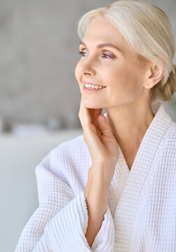 Headshot vertical portrait of smiling middle aged woman wearing bathrobe touching face at spa salon hotel looking away. Bodycare spa procedures skin care antiaging products concept.