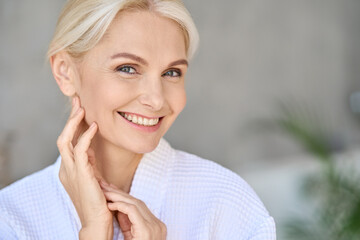 Closeup of happy smiling beautiful middle aged woman spa salon client wearing bathrobe looking at...