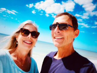 Fototapeta Portrait Of Smiling  Woman And Man On Beach With Blue Sky And Water As Background obraz