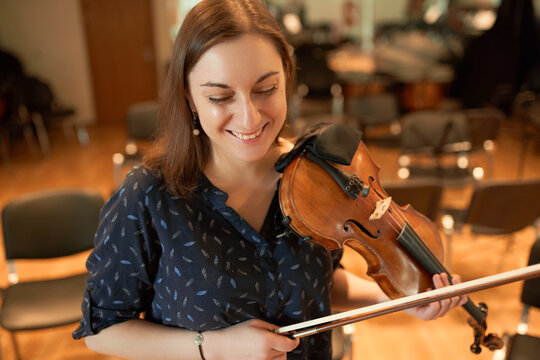 Happy female violinist performing classical music in hall
