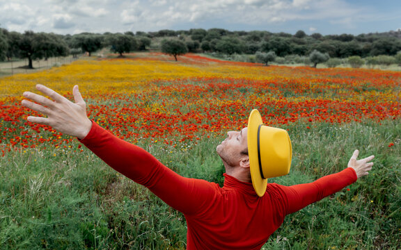 Faceless man in yellow hat outstretching arms in blooming field