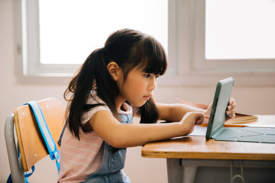 Asian school girl using digital device in school classroom, digital native, technology, learning, touchscreen. Female elementary student with tablet in class.