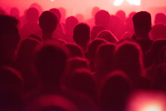 Silhouette of concert crowd at music festival in red stage lights