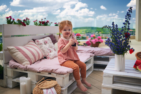 cute toddler baby girl drinking juice on rooftop patio at home, cozy lounge zone handcrafted from wooden pallets