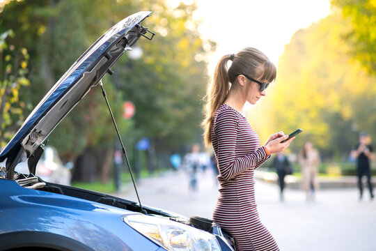 Young upset woman driver talking on mobile phone near a broken car with open hood waiting for help having trouble with her vehicle on a city street.