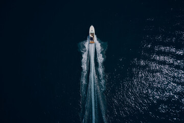 Drone view of a boat sailing. Top view of a white boat sailing to the blue sea. Large white boat fast movement on blue water aerial view. Motor performance boat in the sea. Travel - image. - fototapety na wymiar