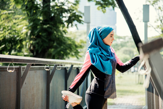 Muslim woman stretching after workout at the park
