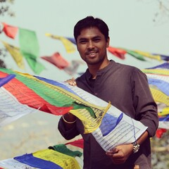 Fototapeta Portrait Of Smiling Young Man Holding Prayer Flags obraz