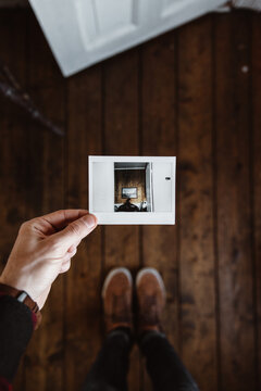 Crop person holding instant picture of room