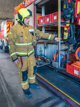 Professional fireman getting ready near fire truck