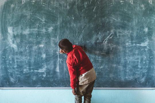 Anonymous black boy writing on chalkboard