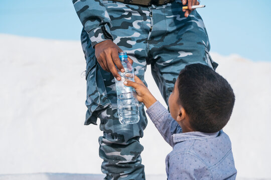 Ethnic boy drinking water near soldier