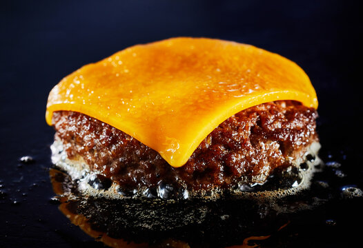 Tasty cheeseburger with beef patty sizzling on a grill