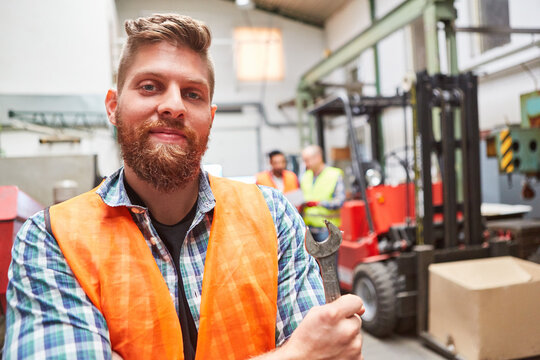 Man as a proud warehouse worker with a wrench