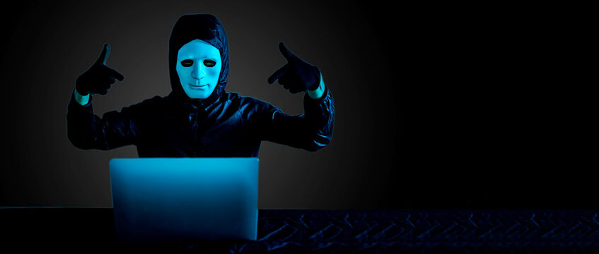 Anonymous computer hacker in white mask and hoodie, professional young male hacker successfully using code designing virus system and raised hands celebrating.