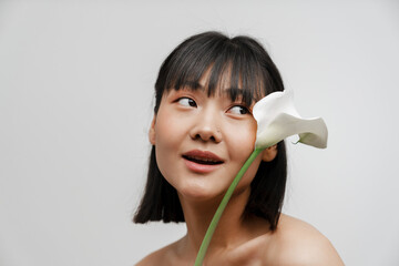 Obraz Young asian shirtless woman with piercing posing wit flower - fototapety do salonu