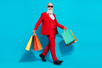 Obraz Full length body size photo aged man keeping packages walking forward isolated vivid blue color background - fototapety do salonu