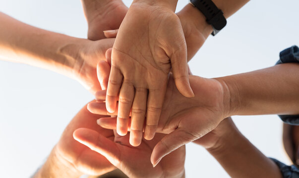 Close up bottom view of people putting their hands together. Friends with stack of hands showing unity and teamwork. Friendship happiness leisure partnership team concept.