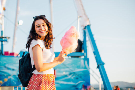 Happy young woman eating cotton candy at fairground