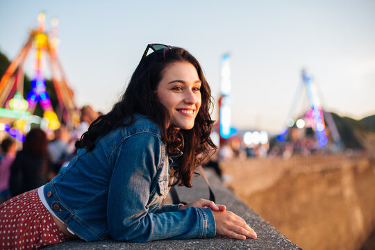 Happy young woman enjoying the sunset at fun fair in summer