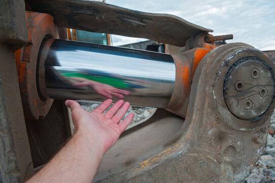 Powerful hydraulic cylinder and human hand.