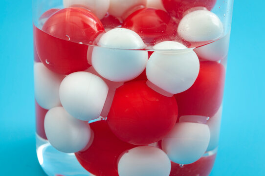 Chemistry backgrounds, chemical bonds and molecular structure of water concept with H2O plastic model molecule (oxygen in red and hydrogen in white) in glass flask isolated on blue background