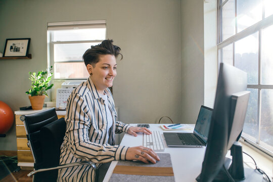 Smiling woman with short hair in striped shirt working on computer in home office