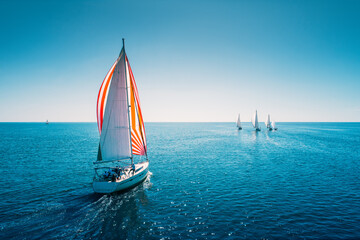 Regatta sailing ship yachts with white sails at opened sea. Aerial view of sailboat in windy condition - fototapety na wymiar