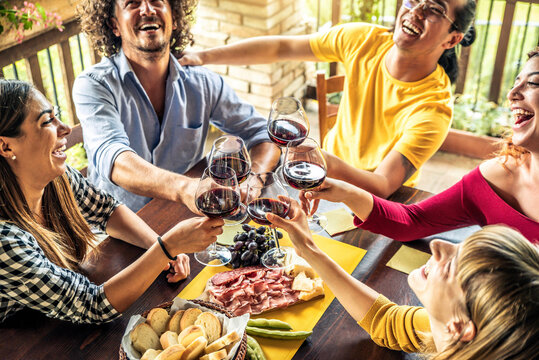 Happy adult friends dining drinking red wine on terrace rooftop home party - Multiracial young people at lunch having fun eating bbq food in gastronomic rustic restaurant - Friendship, youth concept