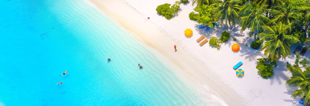 Beautiful summer tropical beach with white sand, palm trees, turquoise ocean water and tourists swimming in clear transparent  turquoise water. Panoramic aerial view. Ultra-wide background image.